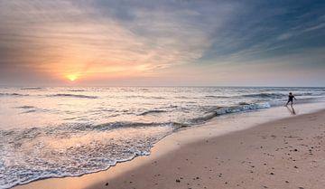 Spelen aan zee tijdens zonsondergang van