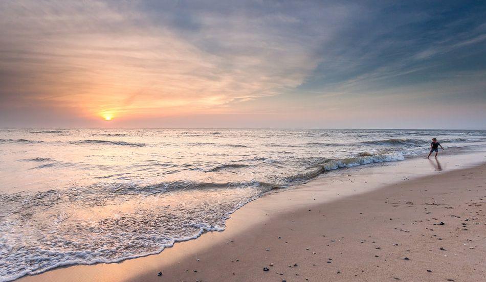 Spelen aan zee tijdens zonsondergang van Martijn van Dellen