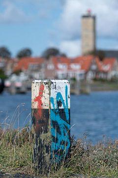 Bont gekleurde houten meerpaal op de havenpier van de haven van Terschelling. van Tonko Oosterink