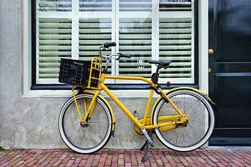 Gele retro-fiets geparkeerd tegen een huis van Tony Vingerhoets