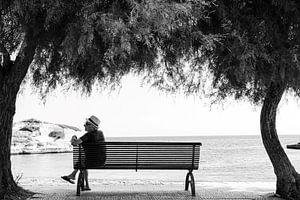 Mann auf einer Bank zwischen Palmen am Strand und Meer in Apulien, Italien von