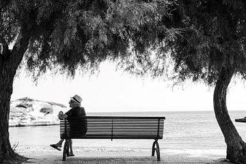 Mann auf einer Bank zwischen Palmen am Strand und Meer in Apulien, Italien von Bianca ter Riet