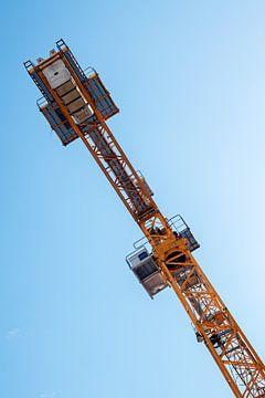 Detail eines Krans vor blauem Himmel, orangefarbene Metallkonstruktion und Betongewichte, Kopierraum von Maren Winter