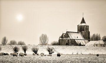 Verschneite St. Martinskirche in Oud-Zevenaar mit Schafen im Vordergrund von LiemersLandschap
