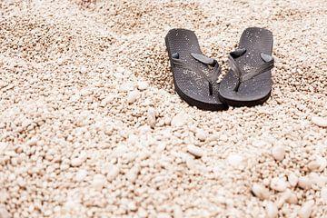 Slippers op kiezelstrand van Victor van Dijk