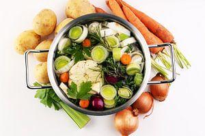 Bouillon met wortelen, uien, diverse verse groenten in een pot - kleurrijke verse heldere lentesoep. van Beats