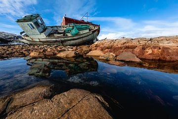 Scheepswrak op de rotsen weerspiegelt in het water van Martijn Smeets