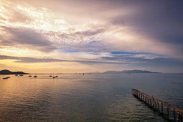 Houten pier in de zee bij zonsondergang in de buurt van Fisherman Village Bophut strand van Tjeerd Kruse