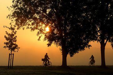 Fietsers en bomen in silhouet in de ochtend bij zonsopgang van Margriet Pflug
