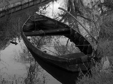 Zwart wit foto van een verlaten roeiboot van Dick de Vries