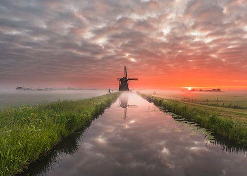 Mooie molen tijdens zonsopkomst in de polder.