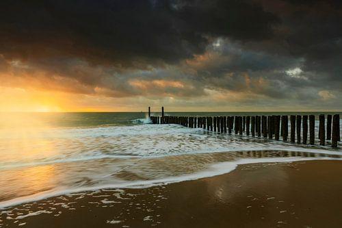 Hollandse wolkenlucht en typische golfbreker van houten palen langs de Zeeuwse kust