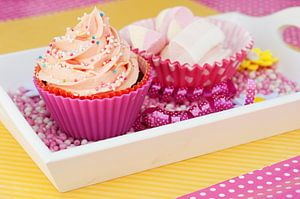 Roze cupcake met spekjes ernaast