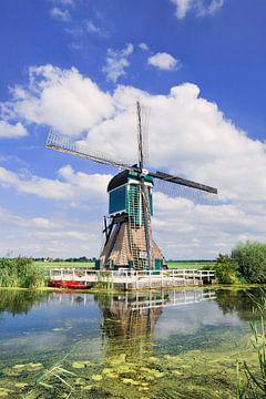 Karakteristiek Nederlandse windmolen dichtbij kanaal met weelderige plantengroei 2 van Tony Vingerhoets