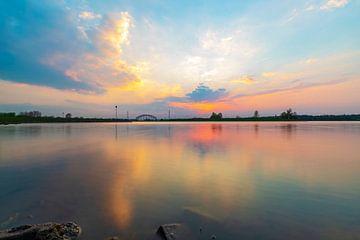 Buntes Abendlicht, das sich im Wasser spiegelt und nach Sonnenuntergang leuchtet. von Arjan Almekinders