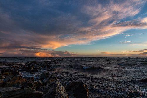 Golfbreker, wolken en zonsondergang