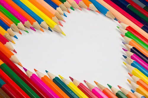 Kleurpotloden in een hartvrom als achtergrond foto