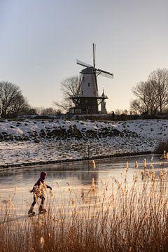 Eenzame schaatser naast molen De Koe