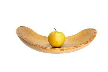 Zijaanzicht van een platte houten schaal met een appel in het midden blootgesteld aan wit van Hans-Jürgen Janda
