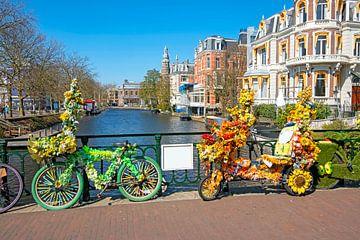Versierde fietsen met bloemen op de gracht in Amsterdam van Nisangha Masselink