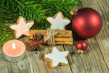 Kerstcompositie van sterrenkoekjes, specerijen, kaarslicht, rode ballen en sparrentakken van Alex Winter