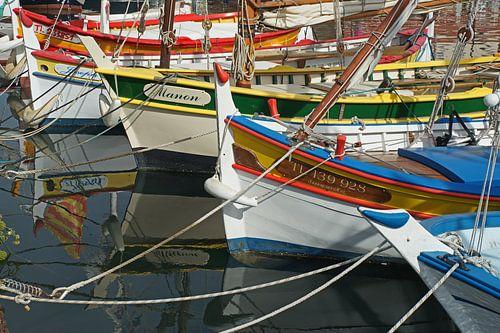 Kleurrijke spiegeling van kleine vissersbootjes in het water van