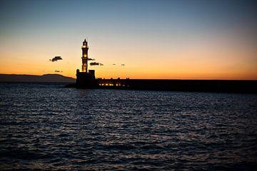 Griekse vuurtoren bij ondergaande zon van