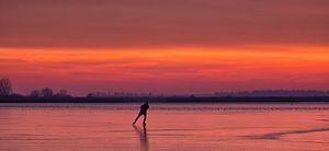 Een schaatser op het ijs van het Lauwersmeer tijdens zonsopkomst in de winter