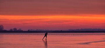 Ein Schlittschuhläufer auf dem Eis des Lauwersmeers bei Sonnenaufgang im Winter von Bas Meelker