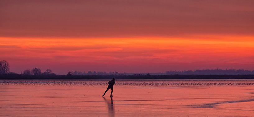 Een schaatser op het ijs van het Lauwersmeer tijdens zonsopkomst in de winter van Bas Meelker