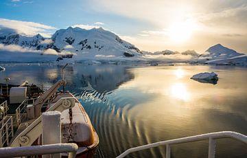 Geruisloos glijdend met een ondergaande zon door Paradise Bay op Antarctica van Thijs van den Burg
