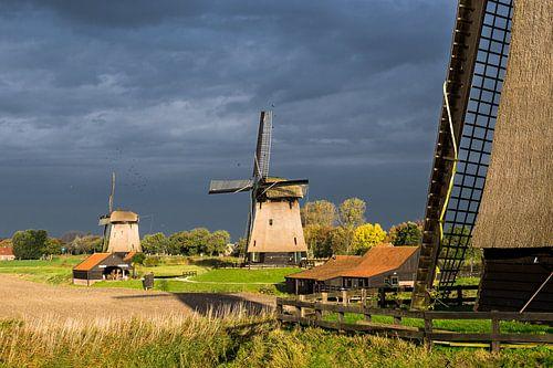 Drie Hollandse molens tegen dreigende lucht