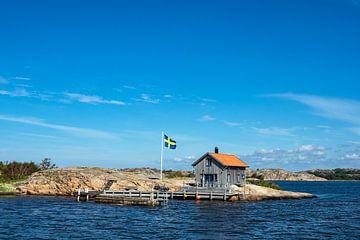 Houten hut en vlag op het eiland Valön voor de stad Fjällbacka in Zweden van Rico Ködder