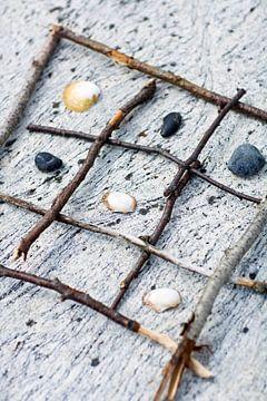 00997969 Tic-Tac-Toe aus Zweigen und Muscheln am Strand von BeeldigBeeld Food & Lifestyle