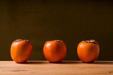 drie sharonfruit op een rij. van Lieke van Grinsven van Aarle