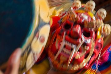 Dynamische weergave van rood masker tijdens dansfestival in Bhutan van Wout Kok