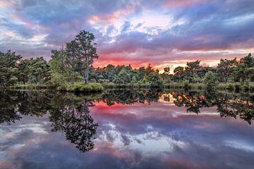 Rustig meer bij zonsondergang met rood gekleurde wolken van Tony Vingerhoets