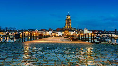 Natte stenen met reflectie met Deventer op de achtergrond tijdens het blauwe uur
