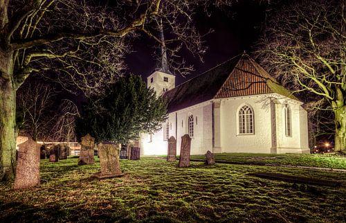 Oude grafzerken van een begraafplaats naast het witte kerkje in Heiloo