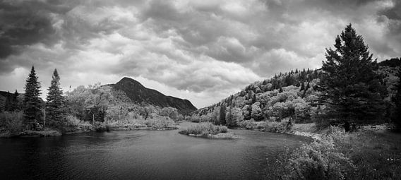 Storm clouds approaching a lake in an autumn forest