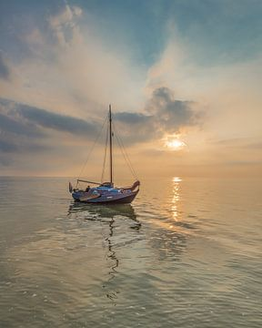 Scheepje vlak voor de haven van Laaxum, Friesland. bij zonsondergang. sur