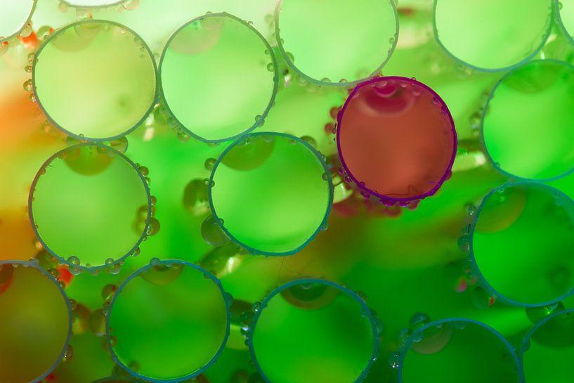 Natte groene rietjes met een paarse daartussen. van Mark Scheper