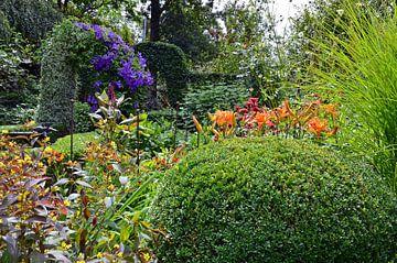 Weelderige tuin met een scala aan groene en bloeiende planten van Gert Bunt