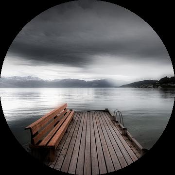 Een mystiek landschap in Noorwegen in zwart-wit met een meer. Een leeg bankje staat op een steiger b van Bas Meelker
