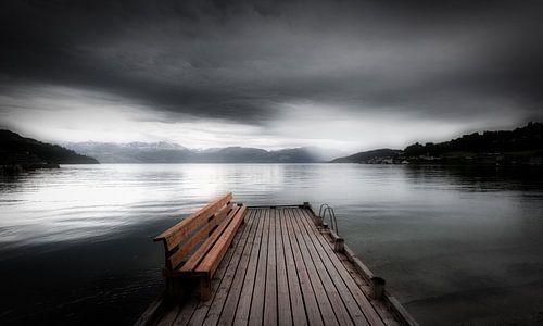 Een mystiek landschap in Noorwegen in zwart-wit met een meer. Een leeg bankje staat op een steiger b