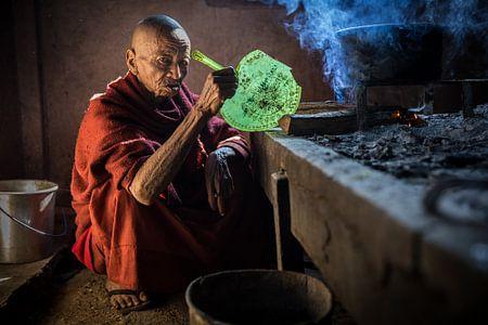 Norse monnik kookt in een ouderwetse keuken in een budhistisch klooster in de omgevinf van Inle in M