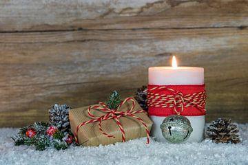 Brandende kaars met kerstgeschenk, dennentak en dennenappels natuurlijke decoratie van Alex Winter