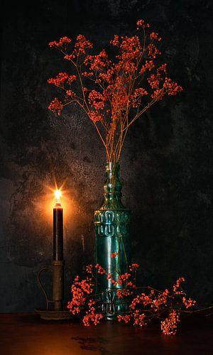 Orange Gypsophila in blauer Flasche und Kerzenlicht.