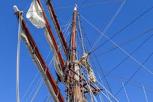 Zeilmast met veel touwen voor een blauwe hemel