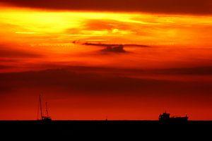 zonsondergang op zee met de silhouetten van 2 boten